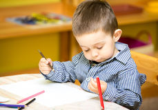Weinig tekening van de kindjongen met kleurrijke potloden in kleuterschool bij lijst in kleuterschool Stock Foto