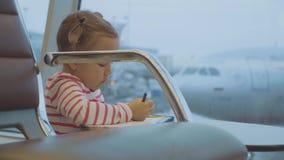 Weinig tekening van het babymeisje bij luchthaven met vliegtuig op de achtergrond stock video