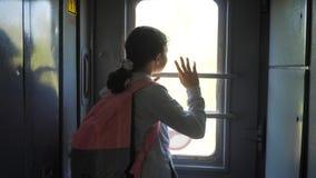 Weinig tiener is een backpacker die door trein reizen de spoorwegconcept van het reisvervoer het meisje van de toeristenschool bi stock video