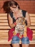 Weinig tijgerbaby op de overlapping van een vrouw royalty-vrije stock afbeelding
