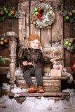 Weinig twee éénjarigenjongen kleedde zich in het jasje, de broek en de laarzen van het braunleer met proefhoed bij het stellen in Stock Fotografie