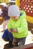 Weinig, twee jaar oude jongens, het spelen vrachtwagenstuk speelgoed in zandbak, vult hij van zand zijn karretjevrachtwagen opnie stock fotografie