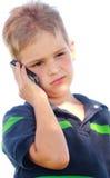 Weinig twijfelachtige jongen op telefoon stock foto