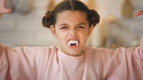 Weinig vampiermeisje die met grote hoektanden enge gezichten maken bij allen zegent Vooravondpartij stock video