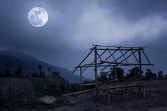 Weinig van bamboehut en berg pieken Silhouetten van bomen met Stock Fotografie