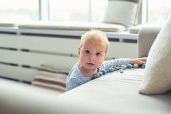 Weinig 8 van de babymaanden jongen bevindt zich thuis met steun dichtbij bank in witte ruimte royalty-vrije stock afbeeldingen