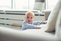 Weinig 8 van de babymaanden jongen bevindt zich thuis met steun dichtbij bank in witte ruimte royalty-vrije stock foto's