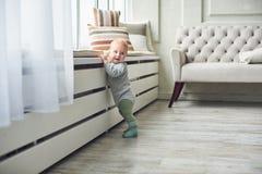 Weinig 8 van de babymaanden jongen bevindt zich thuis met steun dichtbij venster in witte ruimte stock foto's