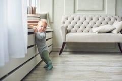 Weinig 8 van de babymaanden jongen bevindt zich thuis met steun dichtbij venster in witte ruimte royalty-vrije stock afbeeldingen