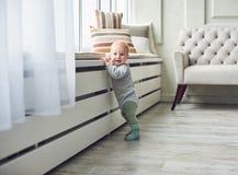 Weinig 8 van de babymaanden jongen bevindt zich thuis met steun dichtbij venster in witte ruimte royalty-vrije stock afbeelding