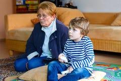 Weinig van de jong geitjejongen en grootmoeder het spelen videospelletje Stock Foto's