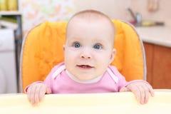 Weinig 7 van het babymaanden meisje op babystoel in keuken Stock Fotografie