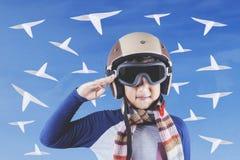 Weinig vliegenier met helm en document vliegtuigen Royalty-vrije Stock Foto