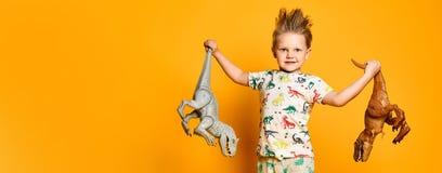 Weinig vrolijke jongen houdt een plastic dinosaurus in elke hand De jongen is gekleed in een kostuum met beelden van dinosaurusse royalty-vrije stock foto's