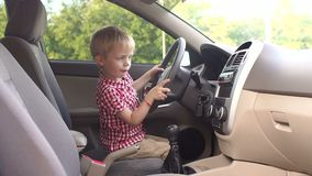 Weinig vrolijke jongen zit het spelen achter het wiel van een auto Langzame Motie stock footage