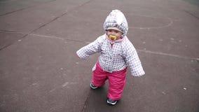 Weinig warm-bekleed kind ongeveer 1 jaar en een maand die over de straat leren te lopen De lente Langzame Motie stock footage