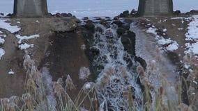 Weinig waterval onder de brug bij de winter wather, close-up een slowmo stock footage