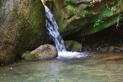 Weinig waterval onder de rotsen van bergkreek royalty-vrije stock foto's