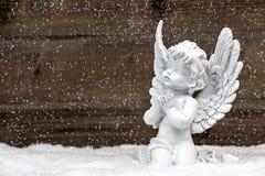 Weinig witte engel op houten achtergrond in sneeuw stock foto