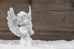 Weinig witte engelen ionen houten achtergrond stock afbeelding