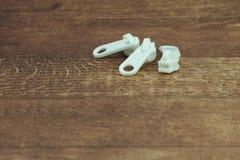 Weinig Witte Plastic Ritssluitingen op Witte Houten Lijst Royalty-vrije Stock Afbeeldingen