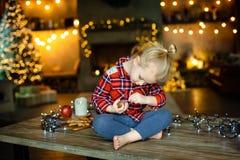 Weinig witte zitting van het blondemeisje op een houten die lijst in de woonkamer van het Chalet, voor Kerstboom wordt verfraaid  stock fotografie