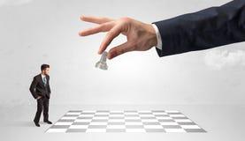 Weinig zakenman het spelen schaak met een groot handconcept royalty-vrije stock foto