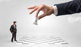 Weinig zakenman het spelen schaak met een groot handconcept vector illustratie
