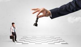 Weinig zakenman het spelen schaak met een groot handconcept stock fotografie