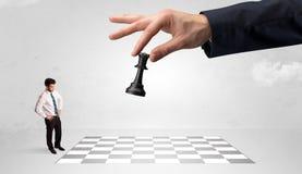Weinig zakenman het spelen schaak met een groot handconcept royalty-vrije stock fotografie