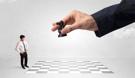 Weinig zakenman het spelen schaak met een groot handconcept royalty-vrije stock foto's