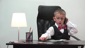Weinig zakenmanportret, elegant grappig kind spreekt op telefoon, tegengeld, werpt van waardeloos bankbiljet stock footage