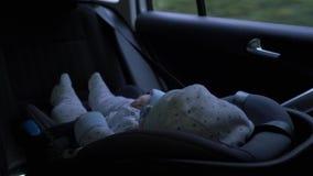 Weinig zitting van de babyjongen in autozetel het berijden in achterbank van auto stock videobeelden