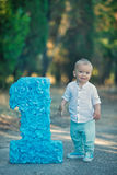 Weinig zitting van de babyjongen dicht bij nummer één de blauwe kleur van het verjaardagsaantal Stock Afbeelding