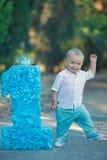Weinig zitting van de babyjongen dicht bij nummer één de blauwe kleur van het verjaardagsaantal Royalty-vrije Stock Foto's