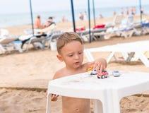 Weinig zitting van de babyjongen op het strand Stock Foto