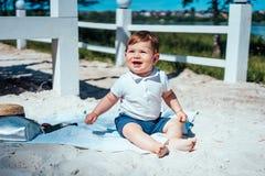 Weinig zitting van de babyjongen op het zand Royalty-vrije Stock Afbeelding