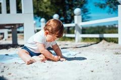Weinig zitting van de babyjongen op het zand Stock Afbeelding