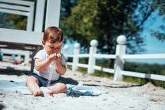 Weinig zitting van de babyjongen op het zand Stock Fotografie