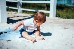 Weinig zitting van de babyjongen op het zand Royalty-vrije Stock Afbeeldingen