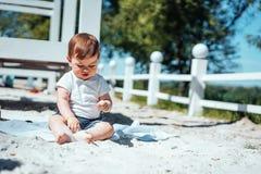 Weinig zitting van de babyjongen op het zand Royalty-vrije Stock Foto's