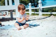 Weinig zitting van de babyjongen op het zand Stock Afbeeldingen