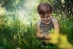Weinig zitting van het babymeisje in gras stock foto