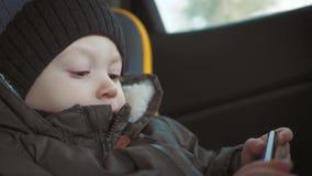 Weinig zitting van jongens verslavende smartphone op bank in stadsstraat Het leuke kind van de babyjongen met mobiele telefoon op stock video