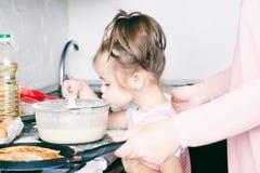 Weinig zoet meisje en haar pannekoeken van het moedergebraden gerecht bij de traditionele Russische vakantie Carnaval Maslenitsa  stock foto