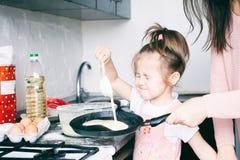 Weinig zoet meisje en haar pannekoeken van het moedergebraden gerecht bij de traditionele Russische vakantie Carnaval Maslenitsa  royalty-vrije stock fotografie