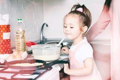 Weinig zoet meisje en haar pannekoeken van het moedergebraden gerecht bij de traditionele Russische vakantie Carnaval Maslenitsa  stock afbeelding
