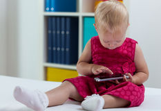 Weinig zoet meisje geinteresseerd in slimme telefoon stock afbeelding