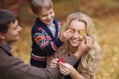 Weinig zoon en papa sluiten ogen aan moeder door bladeren in park royalty-vrije stock afbeelding