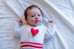 Weinig zuigeling met het stuk speelgoed van de hartvorm op borst stock afbeelding